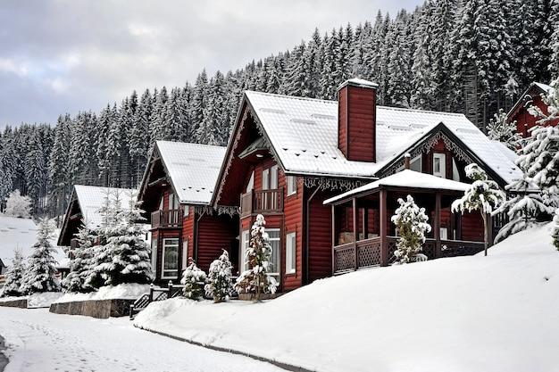 Традиционные деревянные дома на склоне холма в горах карпат в окружении заснеженных елей.