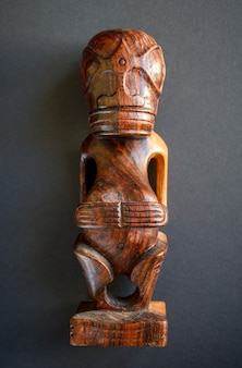 マルケサス諸島の伝統的な木製ポリネシアティキ。暗い背景で隔離