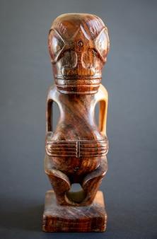 마르키즈 제도의 전통 나무 폴리네시아 티키. 어두운 배경에 고립