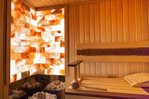 Traditional wooden sauna classic interior empty seats bucket stone brick wall lighting heat stones