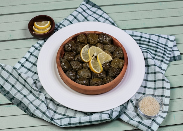Traditional yarpag dolmasi with lemon slices in the white plate.
