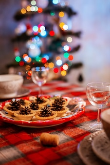 Traditionally decorated christmas table. creative decoration of the festive table cones on a plate on the background of bokeh lights.