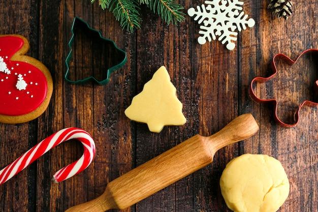クリスマスと新年を祝う伝統。ホリデークッキーの調理、家族の料理。生のジンジャーブレッドクッキーをカットします。