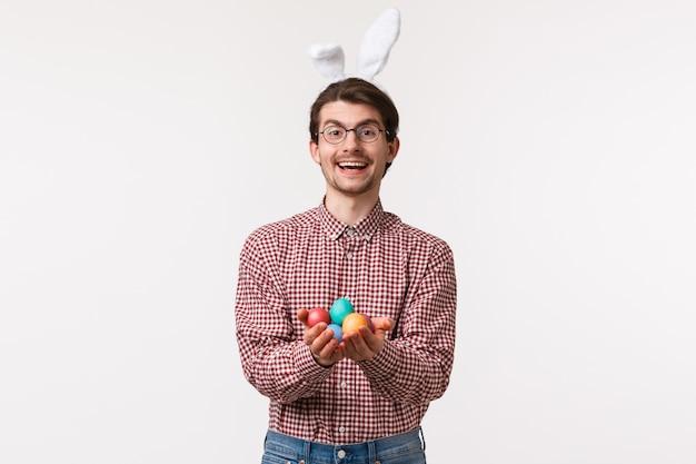전통, 종교 휴일, 축 하 개념. 친절하고 쾌활한 귀여운 기독교 남자, 토끼 귀를 쓰고 페인트 칠한 부활절 달걀을 들고 즐겁게 웃고, 축복의 날을 축하합니다.