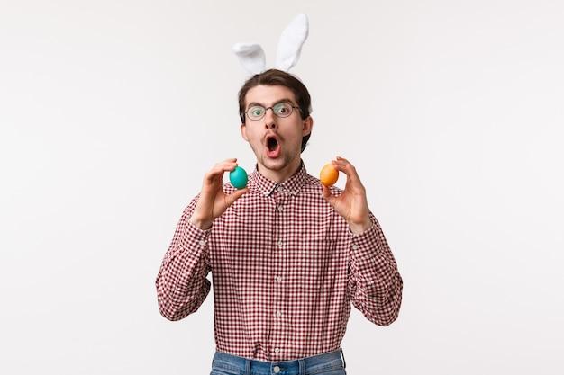 전통, 종교 휴일, 축 하 개념. 안경에 수염을 가진 재미있는 즐거운 젊은이, 귀여운 토끼 귀를 착용하고 부활절 날, 흰 벽에 게임을하는 두 개의 그려진 계란을 잡아