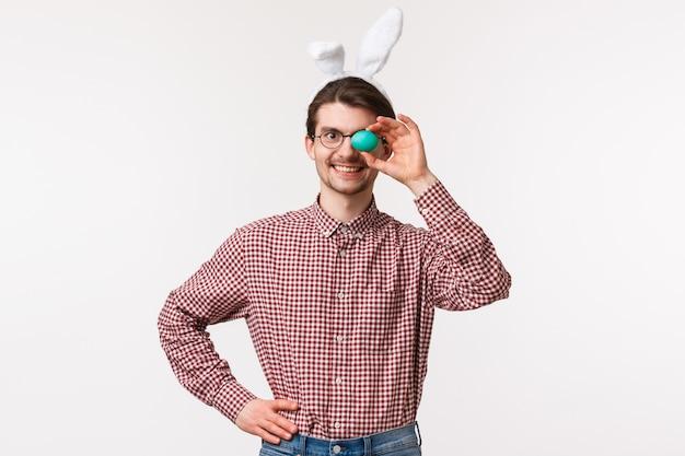 전통, 종교 휴일, 축 하 개념. 토끼 귀에 쾌활한 재미 백인 남자의 허리 업 초상화, 하나의 페인트 계란을 들고 웃 고 만족 부활절 날 식사
