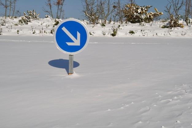 Traffic arrow sign on snow