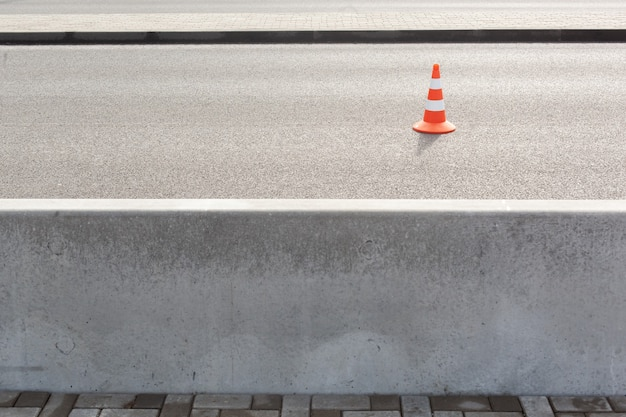 Traffic cone on bitumen pavement road for cars with a large concrete fence separating the road and sidewalk