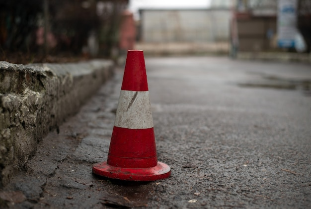 A traffic cone standing on a street along the curbstone of the pavement to prevent other people from parking their cars there.
