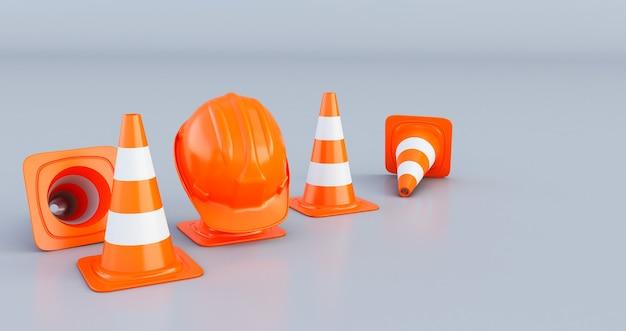 灰色の背景に分離されたトラフィックコーンとオレンジ色のヘルメット