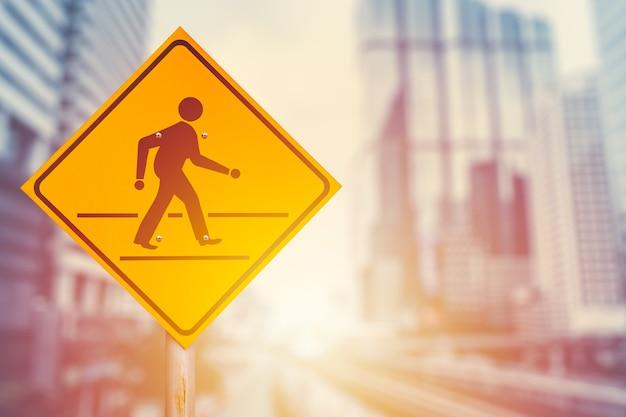 交通横断歩道のサインオンは、現代の市役所の建物の背景をぼかします。コンセプトを歩むビジネスマン。