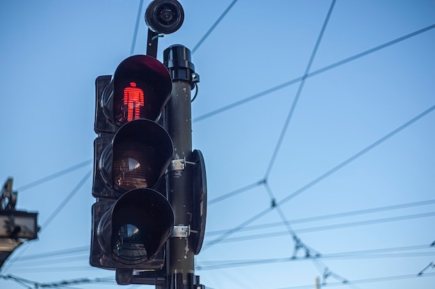 Traffic light detail with red light lit under a blue sky