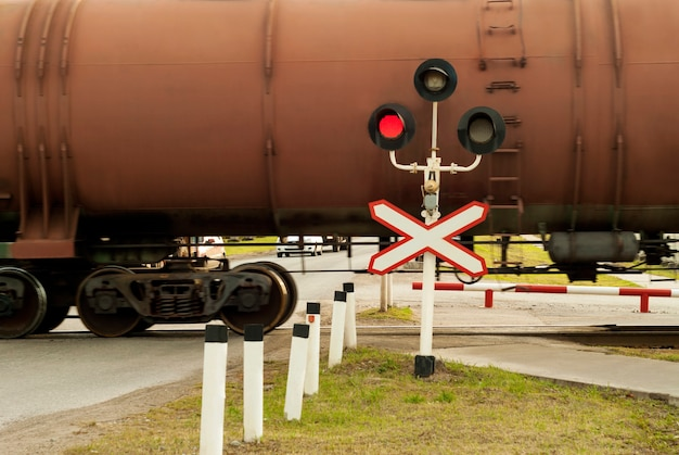 Traffic light and sign on the railway crossing during the passage of freight train with tank wagons