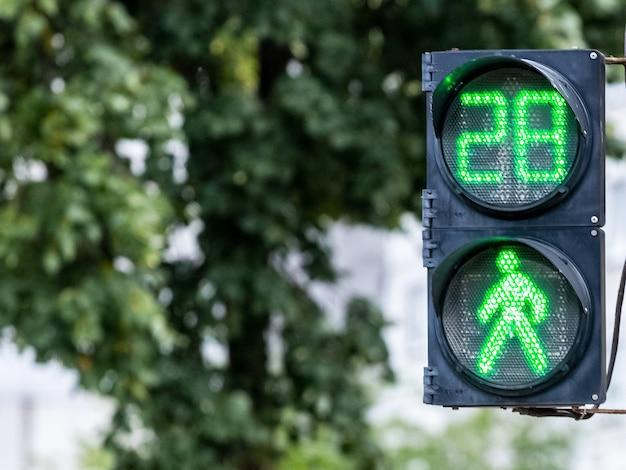 ぼやけた背景に緑色のライトとタイマー付きの信号機。信号は、交通が許可されていることを示します