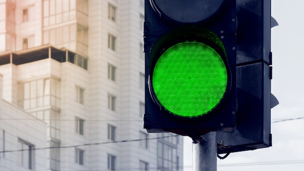 日の出の高層ビルの背景にある都市の緑の光の信号機