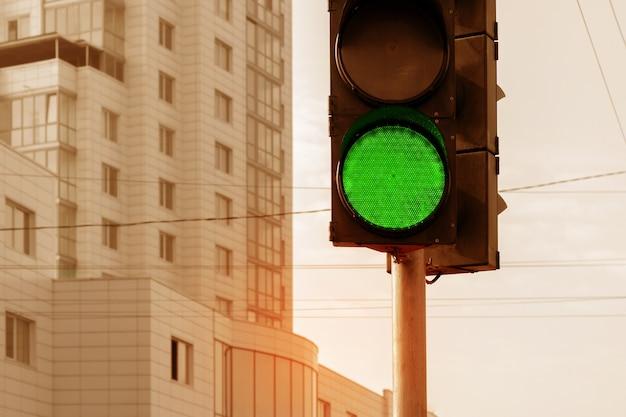 高層ビルを背景にした街の青信号の信号機