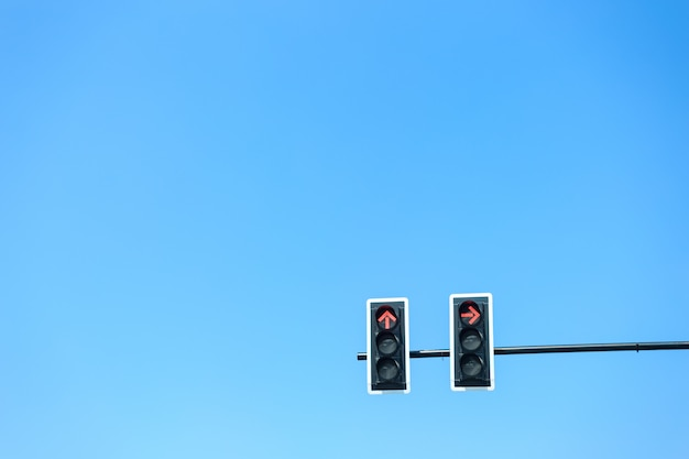 Traffic light with red light against the blue sky