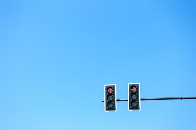青い空を照らす赤信号の信号