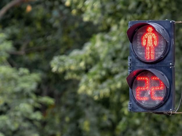 ぼやけた背景に赤いライトとタイマー付きの信号機。信号は交通が禁止されていることを示します