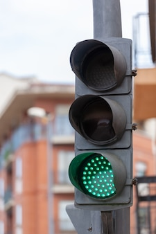 A traffic light with three lights with the green light on allowing the passage of vehicles