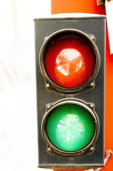 Traffic light with two lights red and green on a red pillar that indicates advance or stop