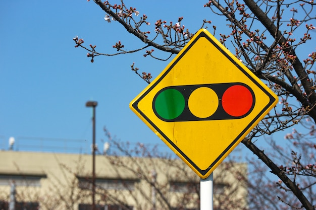 A traffic light yellow board in urban city.