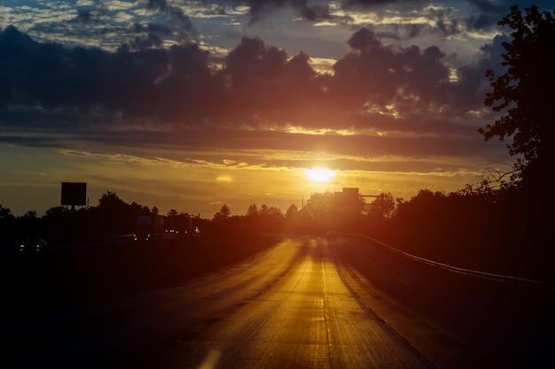 Движение на дороге в красивом восходе солнца небо с облаками