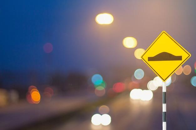 교통 표지 및 defocused 조명 산업에서 도로 배경에 가벼운 자동차로 나뭇잎있다