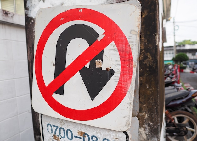 Traffic sign of no u-turn on the road in the town.