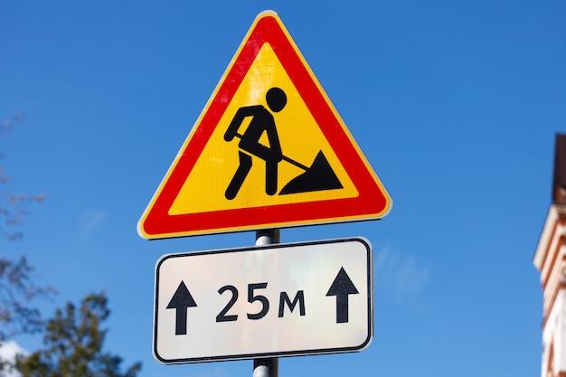 교통 표지판. 노란색 배경에 삽을 든 인간의 모습이 있는 빨간색 삼각형. 건설 작업. 고품질 사진