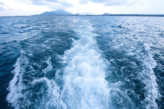 Trail and foamy waves on blue sea surface behind of moving boat with island background.