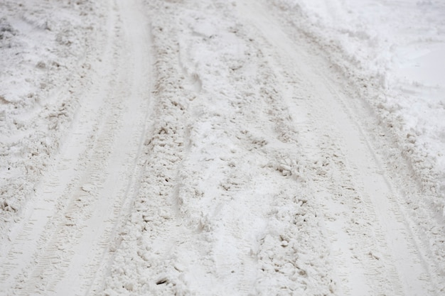 雪の中で車のタイヤからトレイル。未回収のウィンターロード。高品質の写真