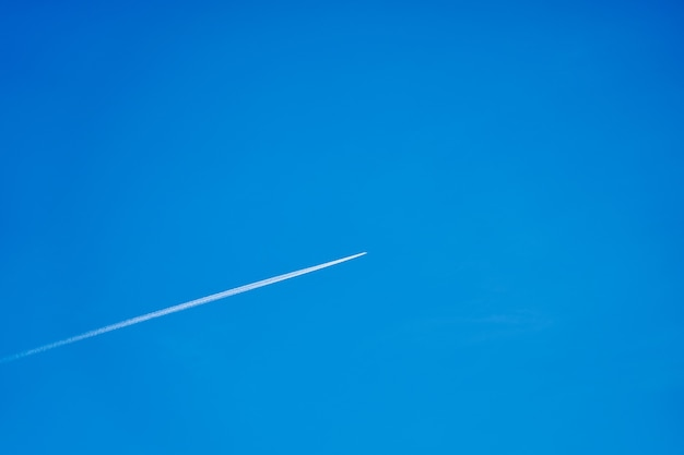 A trail from the plane in the blue clear sky.