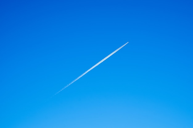 Trail from the plane in the blue sky.