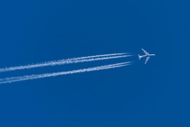 青い空に4つのエンジンを搭載した飛行機からのトレイル。
