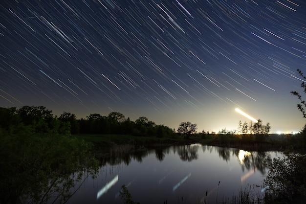 호수 위에 북극성 주변의 밤하늘에 별의 흔적. 장시간 노출로 촬영