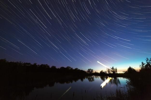 湖の上の北極星の周りの夜空の星の軌跡
