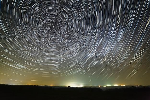 След звезд в ночном небе вокруг полярной звезды. снято с длинной выдержки освещенного города.