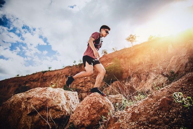 Trail runner jumping on the horizon and stone