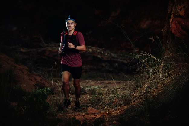 Trail runner running on the rocky road in the night
