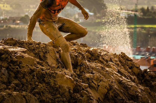 Trail running athlete crossing the dirty puddle in a mud racer.