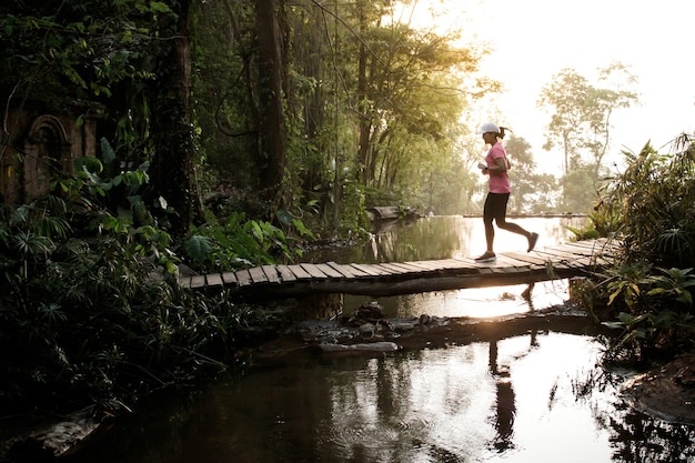 Trail running athlete moving through the bridge in the rural road.