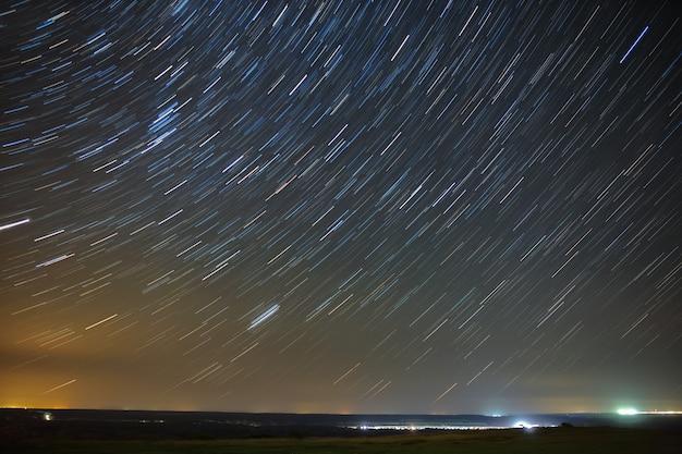 도시 위로 빛나는 polar star 주변의 트레일 별.