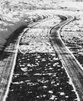 The trail of the tires on a snowy road, a black and white monochrome photo