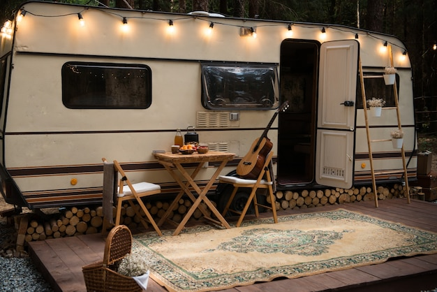 Trailer parked in camping decorated with light garlands and carpet on wooden platform