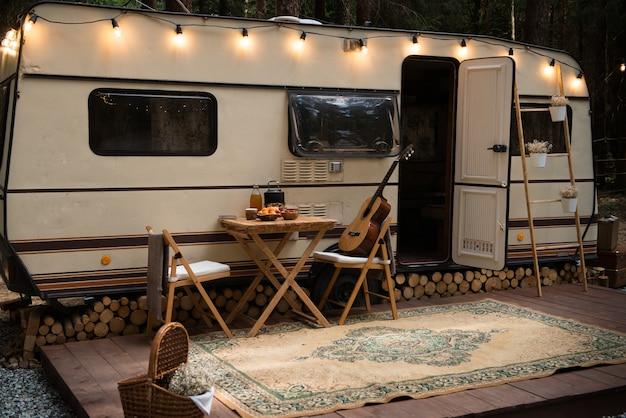 木製のプラットフォームに明るい花輪とカーペットで飾られたキャンプに駐車したトレーラー