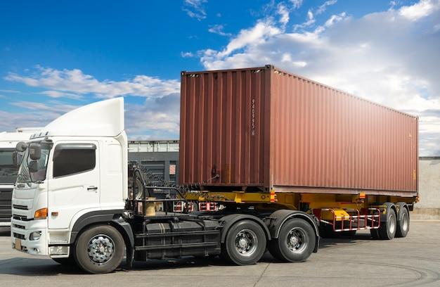 푸른 하늘 산업 화물 트럭 운송에서 화물 컨테이너 주차가 있는 트레일러 트럭