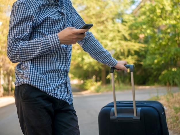 手荷物と電話を使用して街の通りでカジュアルなtrailingの10代の若者