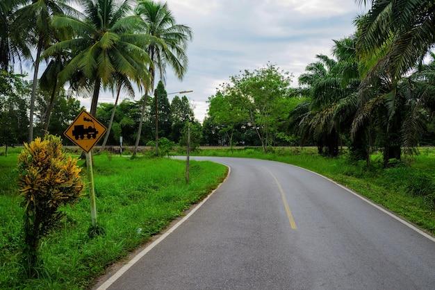 Железнодорожные и железнодорожные предупреждающие желтые знаки на изогнутой местной дороге в сельской местности