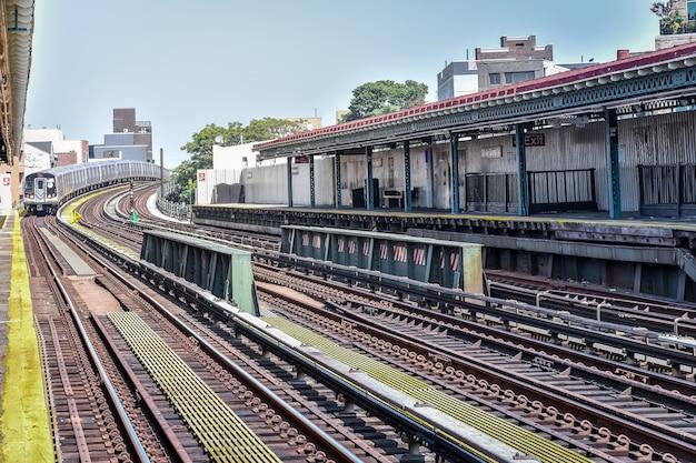 Поезд прибывает на вокзал нью-йорка. здания на заднем плане, городской пейзаж. концепция путешествий и транзита. манхэттен, нью-йорк, сша.